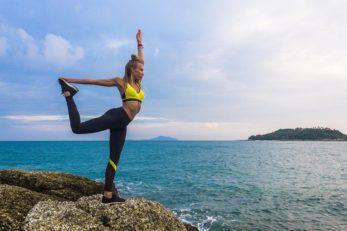 Woman dong yoga near the ocean. Sporty woman doing yoga at the sea. Horizontal outdoors shot.